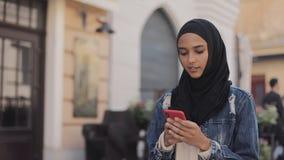 Młoda muzułmańska kobieta jest ubranym hijab chustki na głowę odprowadzenie w centrum miasta i używa smartphone Komunikacja, onli zdjęcie wideo
