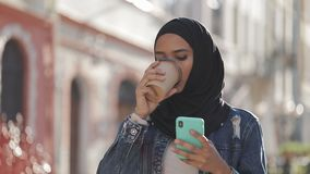 Młoda muzułmańska kobieta jest ubranym hijab chustki na głowę odprowadzenie w centrum miasta, używa smartphone i pije kawę, zdjęcie wideo