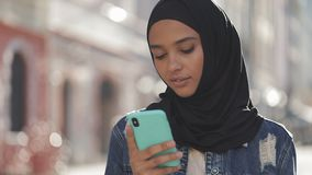 Młoda muzułmańska kobieta jest ubranym hijab chustki na głowę pozycję w centrum miasta i używa smartphone Komunikacja, online zbiory wideo