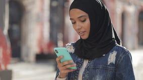 Młoda muzułmańska kobieta jest ubranym hijab chustki na głowę pozycję w centrum miasta i używa smartphone Komunikacja, online zbiory