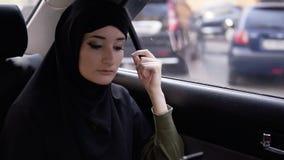 Młoda muzułmańska kobieta patrzeje jej telefon podczas wycieczki samochodem Zamyślenie patrzeje na ulicie przez samochodu zbiory