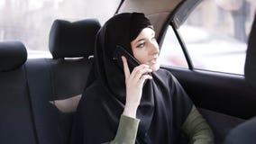 Młoda muzułmańska kobieta w czarnym hijab obsiadaniu w samochodzie na pasażerskim tylni siedzeniu i opowiadać na telefonie komórk zbiory