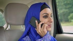 Młoda muzułmańska kobieta w hijab obsiadaniu w samochodzie na pasażerskim tylni siedzeniu i opowiadać na telefonie komórkowym, on zdjęcie wideo