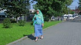 Młoda Muzułmańska kobieta w lekkim szaliku w parku pije kawę zdjęcie wideo