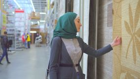 Młoda muzułmańska kobieta wybiera dywan zbiory wideo