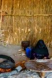 Młoda muzułmańska kobieta z zamaskowanej twarzy kulinarnym chlebem w beduińskim mieszkaniu zdjęcia stock