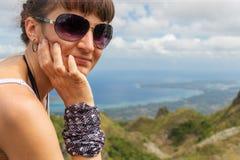 Młoda myśląca kobieta z okularami przeciwsłonecznymi siedzi jeden góry i patrzeje kamerę Fotografia Stock