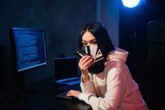 Młoda nastolatka hackera dziewczyna trzyma kredytową kartę narusza intymnego hasło trzyma kredytową kartę w cyberprzestępstwie w  fotografia royalty free