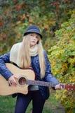 Młoda nastoletnia dziewczyna bawić się gitarę w parku Zdjęcia Royalty Free