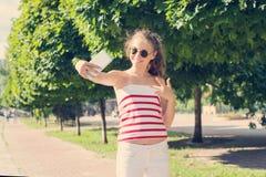 Młoda nastoletnia dziewczyna ma zabawę z telefonem, bierze wideo, bierze selfie fotografia royalty free