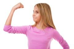 Młoda nastoletnia dziewczyna pokazuje jej mięśniową rękę odosobniony obrazy stock
