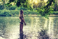 Młoda nastoletnia dziewczyny pozycja w płytkim rzecznym jest ubranym bikini zdjęcia stock