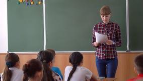 Młoda nauczyciel kobieta przed klasą przy blackboard zbiory