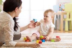 Młoda niania bawić się z małym dzieckiem, indoors obrazy royalty free