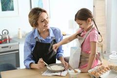 Młoda niania z śliczną małą dziewczynką gotuje wpólnie zdjęcia stock