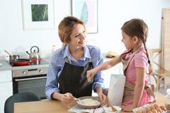 Młoda niania z śliczną małą dziewczynką gotuje wpólnie fotografia stock