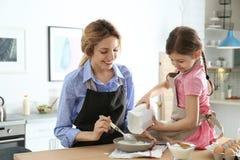 Młoda niania z śliczną małą dziewczynką gotuje wpólnie obrazy stock