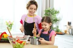 Młoda niania z ślicznym małej dziewczynki kucharstwem zdjęcia stock