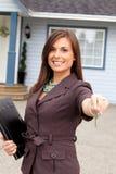 Młoda nieruchomości kobieta wręcza klucz Zdjęcia Royalty Free