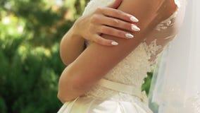 Młoda niezidentyfikowana panna młoda w białej sukni z pięknym manicure'em i zbiory