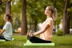 Młoda nikła dziewczyna siedzi w lotosowej pozycji z przymknięć oczami robi ćwiczeniom z innymi dziewczynami na zielonej trawie w obraz royalty free
