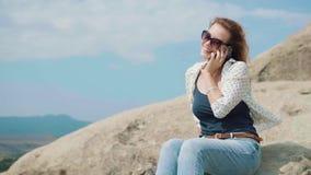 Młoda nikła kobieta w krótkich cajgach i białych sneakers chodzi samotnie nad skałami w Gruzja, aktywnym i ekstremum młodości, zdjęcie wideo