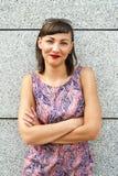 Młoda nowożytna kobieta przeciw ścianie w mieście ono uśmiecha się camer obrazy stock