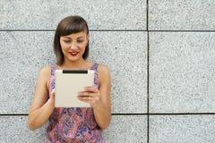 Młoda nowożytna kobieta używa pastylkę w mieście ścianą, ono uśmiecha się Obrazy Royalty Free
