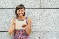 Młoda nowożytna kobieta używa pastylkę w mieście ścianą, ono uśmiecha się Fotografia Stock