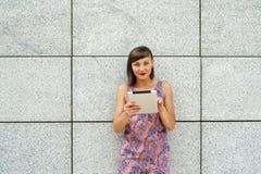 Młoda nowożytna kobieta używa pastylkę w mieście ścianą, ono uśmiecha się Fotografia Royalty Free