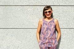 Młoda nowożytna kobieta w okularach przeciwsłonecznych ścianą w mieście ono uśmiecha się przy obraz royalty free