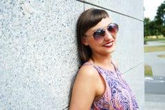 Młoda nowożytna kobieta w okularach przeciwsłonecznych ścianą w mieście ono uśmiecha się przy obraz stock