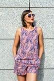 Młoda nowożytna kobieta w okularach przeciwsłonecznych ścianą w mieście ono uśmiecha się przy fotografia stock