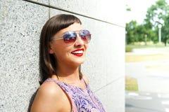 Młoda nowożytna kobieta w okularach przeciwsłonecznych ścianą w mieście ono uśmiecha się przy zdjęcia royalty free