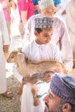 Młoda Omani chłopiec trzyma dziecka koźli zdjęcia stock