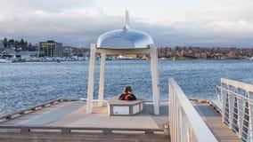 Młoda osoba jest odpoczynkowa pod miniaturowym zabytkiem blisko jeziora po środku dużego miasta obrazy stock
