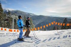 Młoda para kobiety cieszy się narciarstwo przy ośrodkiem narciarskim obraz royalty free