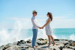 Młoda para kochankowie, facet i dziewczyna na oceanie w biel ubraniach na kamieniach, fotografia stock