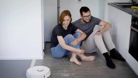 Młoda para małżeńska bada nowego robota próżniowego cleaner Mądrze domowi przyrząda zdjęcie wideo