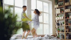 Młoda para małżeńska jest skacząca i tanczący na dwoistym łóżku w lekkim pokoju z wielkimi okno, szczęśliwi ludzie mają zabawę zbiory wideo