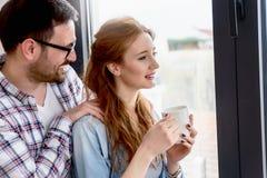 Młoda para małżeńska stoi bezczynnie okno ich nowy mieszkanie fotografia stock