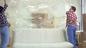Młoda para małżeńska usuwa ceratę od kanapy po tym jak poruszający wolny mo zdjęcie wideo