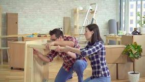 Młoda para małżeńska zbiera wezgłowie stół w nowym nowożytnym mieszkaniu zdjęcie wideo