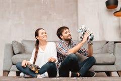Młoda para siedzi na podłoga w żywym pokoju Facet trzyma robot Zdjęcia Stock
