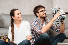 Młoda para siedzi na podłoga w żywym pokoju Facet trzyma robot Obraz Royalty Free
