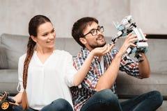 Młoda para siedzi na podłoga w żywym pokoju Facet trzyma robot Zdjęcie Royalty Free