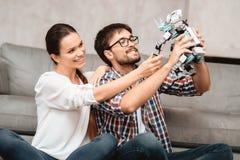 Młoda para siedzi na podłoga w żywym pokoju Facet trzyma robot Zdjęcie Stock