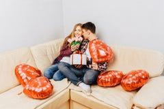 Młoda para w miłości, mężczyzna gratuluje kobiety dawać ona bukietowi tulipany i prezent, siedzi w domu na kanapie fotografia royalty free