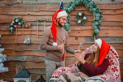 Młoda para w Santa kapeluszach, w domu, trzyma szkła z szampanem w ich rękach zdjęcie royalty free