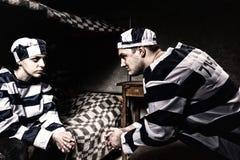 Młoda para więźniowie jest ubranym więzienia jednolitego obsiadanie kibel i Obrazy Stock